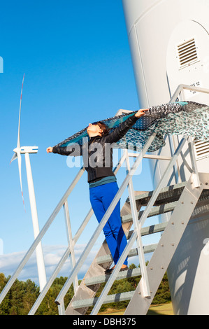 An image of girl holding canvas-cape and windturbine in background - Stock Photo