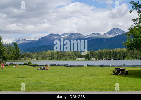Green lawn, sunbathers and picnic tables at Rainbow Park on Alta Lake in Whistler, Canada.  Forest and mountains - Stock Photo