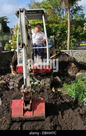 Mini digger removing earth in domestic garden - Stock Photo