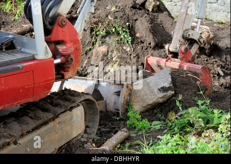 Mini digger moving earth in domestic garden - Stock Photo