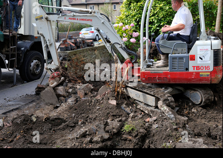 Mini digger working in domestic garden removing stone wall and soil - Stock Photo