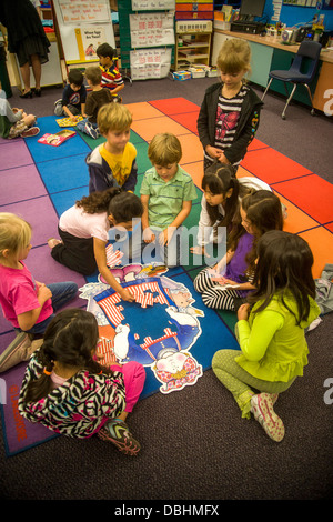 On a classroom floor, a group of kindergarten children collaborate to assemble a jigsaw puzzle in San Clemente, - Stock Photo