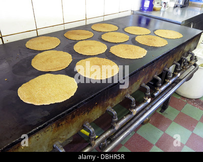 Interior of a traditional Stoke / Staffordshire Oatcake shop, with bright yellow frontage, cooking on an iron griddle - Stock Photo