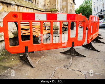 Safety barriers on a British pavement sidewalk in central York, UK after benches were varnished and painted. - Stock Photo