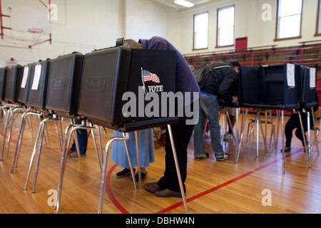 People casting their vote in a school gymnasium, USA, 2012 election day. - Stock Photo