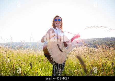 Teenage girl wearing dark glasses playing a guitar in a grassy field. Outdoors. Summer. - Stock Photo