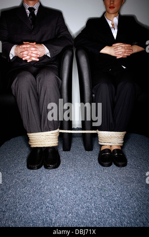Male and female business people's legs tied - Stock Photo