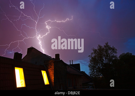 lightning storm with bolts above the rooftops of row houses - Stock Photo