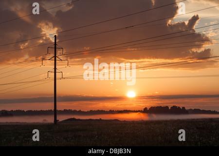 Power line, fog and sunset over farm house - Stock Photo