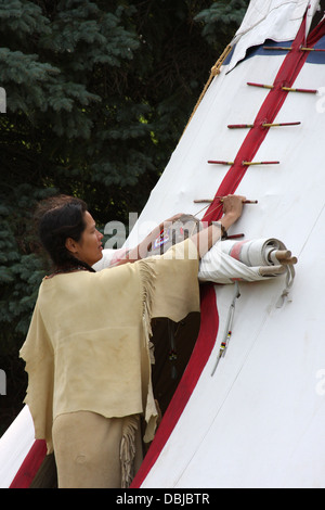 Native American Indian woman breaking down a tipi to move - Stock Photo