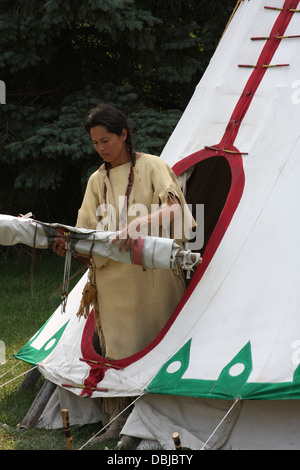Native American Lakota Indian woman removing the door flap from a tipi - Stock Photo