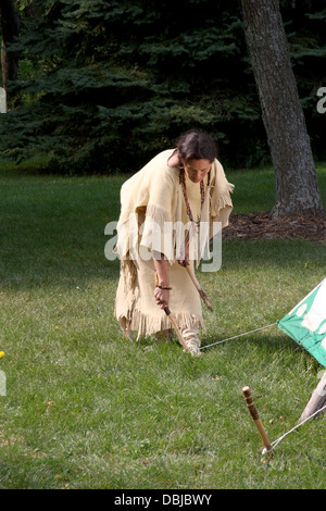 Native American Lakota Indian woman removing the tent stakes from a tipi - Stock Photo