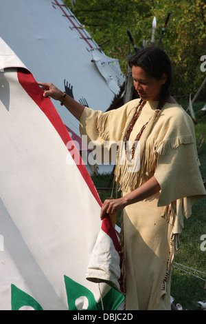 Native American Lakota Indian woman removing tent sides from a tipi - Stock Photo