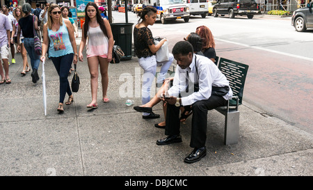 scantily clad young women pedestrians pass stylishly dressed young black man sitting on sidewalk bench East 34th - Stock Photo