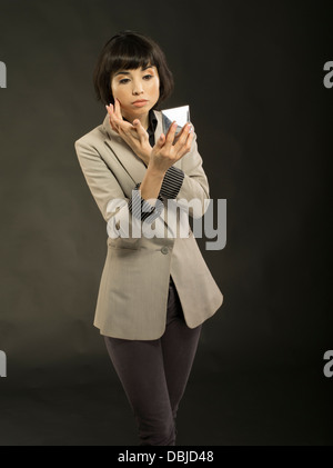 Young beautiful woman in her twenties checking makeup in mirror inside compact - Stock Photo