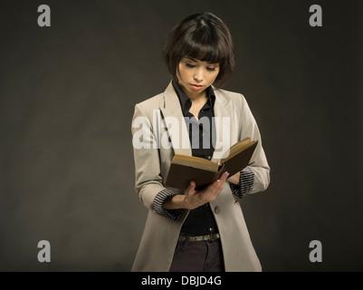 Young beautiful woman in her twenties reading old hardback book - Stock Photo