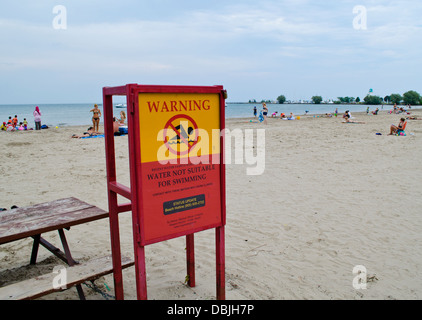 On the sandy beach, a sign warns against swimming in Lake Ontario due to high bacteria levels, pollution, or turbidity. - Stock Photo