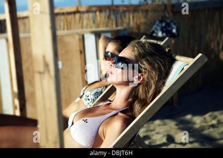 Young Women Sunbathing On Beach - Stock Photo