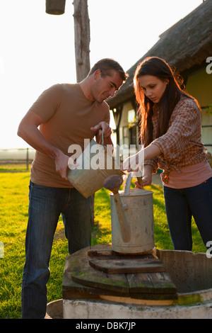 Young Couple On Farm Pouring Water In Bucket, Baranja, Croatia, Europe - Stock Photo