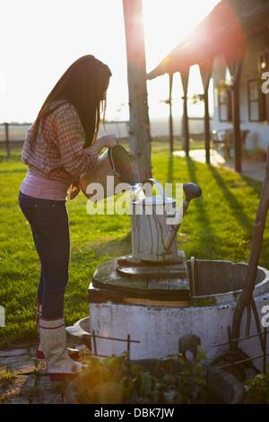 Young Woman On Farm Pouring Water in Bucket, Baranja, Croatia, Europe - Stock Photo