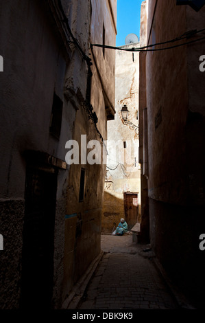 Woman begging in a narrow street of the medina. Fez el Bali, Fez, Imperial city, Morocco - Stock Photo