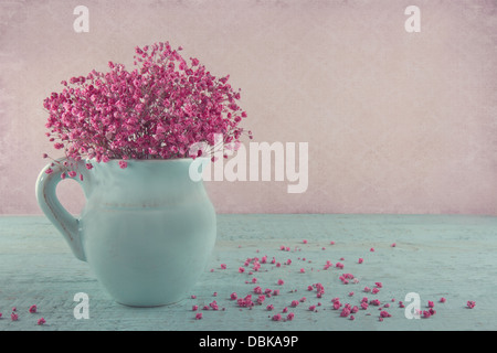 Pink dried baby's breath flowers in a blue jug on wooden background and vintage wallpaper - Stock Photo