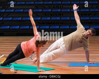 Man and woman doing Pilates exercises - Stock Photo