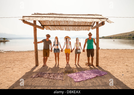 Croatia, Five young people on beach, side by side - Stock Photo