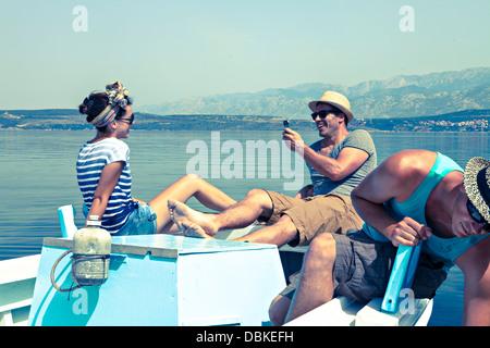 Croatia, Dalmatia, Young people in a boat, relaxing - Stock Photo