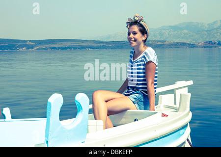 Croatia, Dalmatia, Young woman in a boat, relaxing - Stock Photo