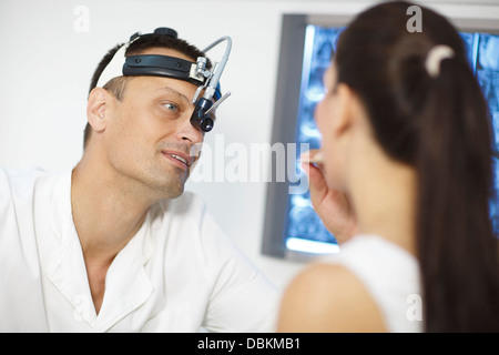 ENT physician Examines the Throat of a Female Patient - Stock Photo