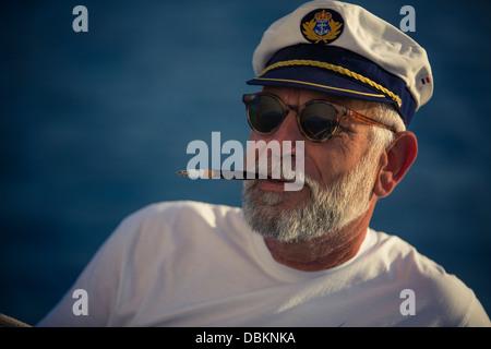 Croatia, Senior man with captain's hat smoking, portrait - Stock Photo