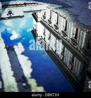 Reflection of the HM Treasury building in a puddle with a Union Jack flag London England UK  KATHY DEWITT - Stock Photo