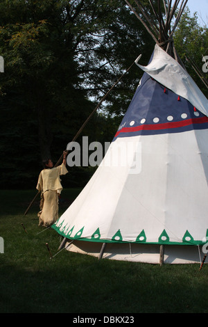 Native American Indian woman removing flap vent poles from a tipi - Stock Photo