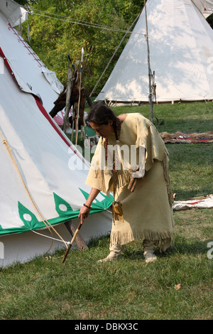 Native American Lakota Indian woman pulling stakes up from a tipi - Stock Photo