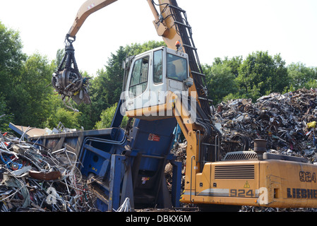 crane loading scrap metal into compactor at scrapyard for baling before being transported for re-smelting united - Stock Photo