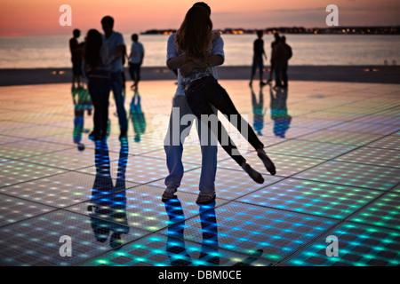 Croatia, Dalmatia, Solar panels as a dance floor, sunset in background - Stock Photo