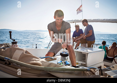 Croatia, Adriatic Sea, Young men on sailboat - Stock Photo
