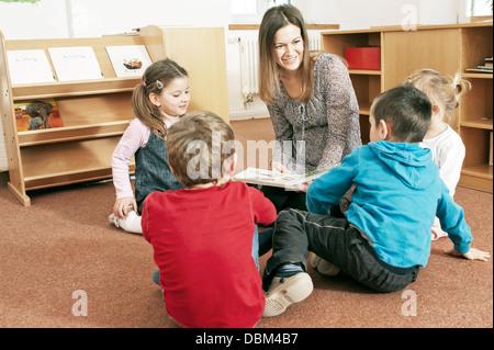 Female Teacher With Children in Classroom, Kottgeisering, Bavaria, Germany, Europe - Stock Photo