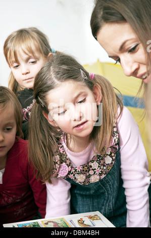 Teacher And Children In Nursery School, Kottgeisering, Bavaria, Germany, Europe - Stock Photo
