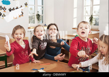 Children In Nursery School Throwing Paper Planes In The Air, Kottgeisering, Bavaria, Germany, Europe - Stock Photo