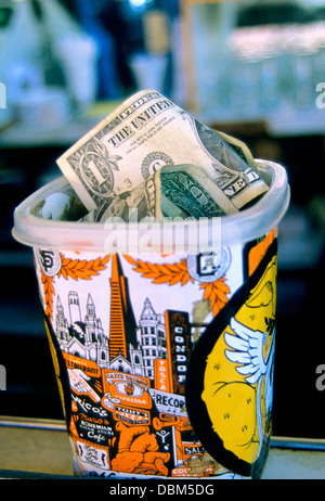 close up of tip jar stuffed with money  at cafe trieste in North Beach San francisco - Stock Photo
