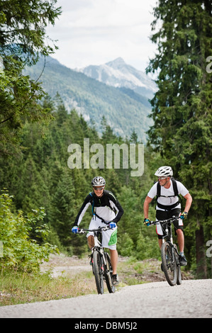 Two mountain bikers riding on road, Chiemgau, Bavaria, Germany - Stock Photo