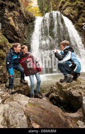 Three Children In Front Of A Waterfall, Bavaria, Germany, Europe - Stock Photo