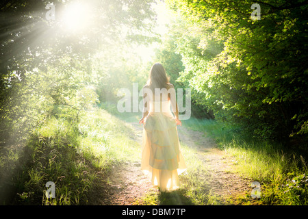Beautiful young fairy woman walking on a path in a magical enchanted forest with dreamy beams of light shining over - Stock Photo