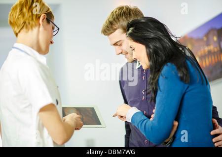 Female doctor explains diagnosis, using a digital tablet, Osijek, Croatia - Stock Photo