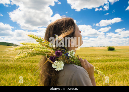 beautiful young woman in holding a bunch of wild flowers enjoying dbm8mn