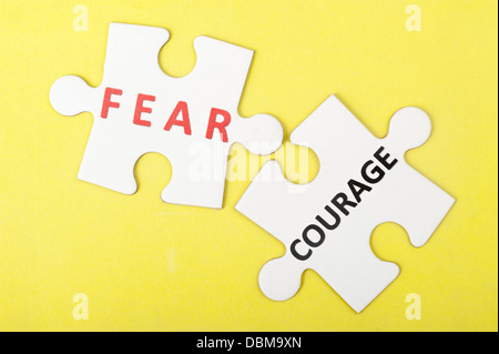 Fear versus courage concept with two pieces of jigsaw puzzle - Stock Photo