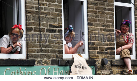Three women in 1940s clothing watching the crowds . Haworth 1940s Weekend . Haworth West Yorkshire England . - Stock Photo