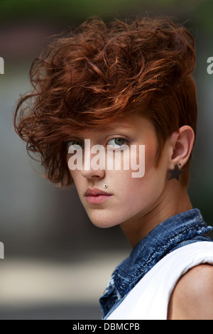 Fashionable teenage hipster girl with lip ring piercing and spiked trendy accessories posing. This is how teenagers - Stock Photo